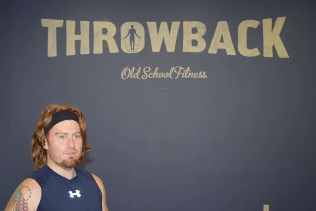 Griffin in front of Throwback Fitness sign