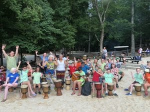 participants signing with drums on a beach