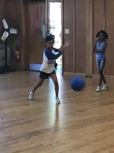 goalball player throwing a blue ball