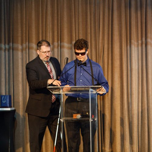 Robert Mead helping his son Andrew Mead-Colegrove get situated on stage.