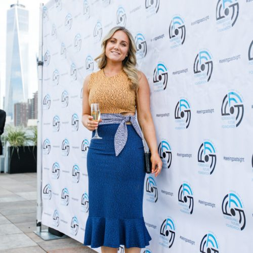On the roof for cocktail hour, a woman stands in front of our step and repeat.
