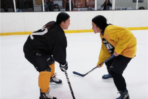 Photo of Melissa and fellow hockey team mate on the ice practicing.